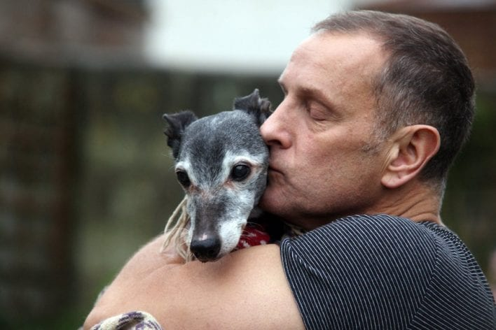 Mark Woods kisses his dog Walnut before taking him to Porth beach for a final walk, November 12 2016. See SWNS story SWWALNUT; Hundreds of animal lovers turned out yesterday (at) to support a heartbroken dog owner as he took his beloved pet on its final walk. Mark Woods stole the nation's heart after he appealed for fellow dog lovers to join him on his last walk with Walnut, the 18-year-old whippet he has has had since a puppy. Hordes of well-wishers, many accompanied by their own dogs, joined Mark and his family on a wind swept Porth beach, Newquay in Cornwall for Walnut's emotional farewell. Mark carried Walnut across the beach as his health has deteriorated in old age and he's no longer able to walk.